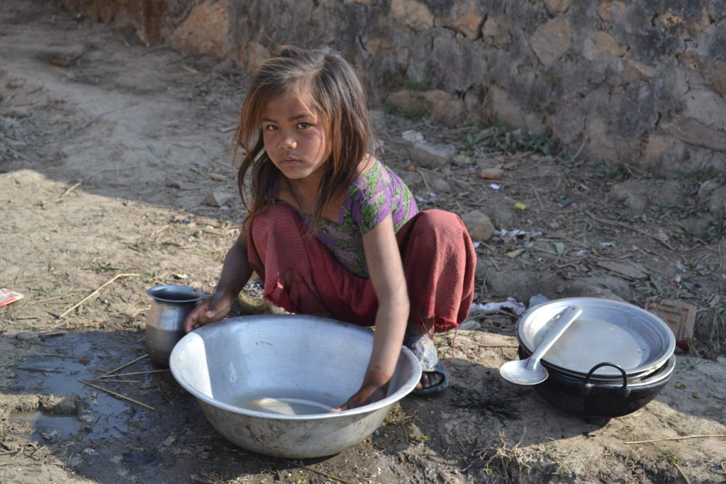 A photograph of a brick child cleaning pots in the open air